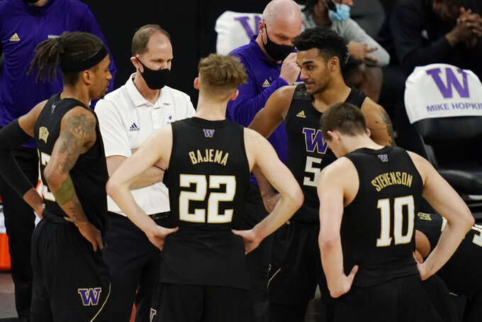 Washington head coach Mike Hopkins speaks with his players during the second half of an NCAA college basketball game in the first round of the Pac-12 men's tournament Wednesday, March 10, 2021, in Las Vegas. (AP Photo/John Locher)