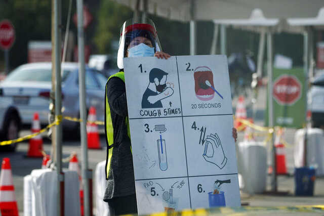 FILE - In this Jan. 5, 2021 file photo, a worker gives instructions to motorists at a COVID-19 testing site in Los Angeles.  The pandemic has caused many people to reassess their priorities. There is talk of moving out of the city, simplifying life and saving more money.  (AP Photo/Marcio Jose Sanchez)