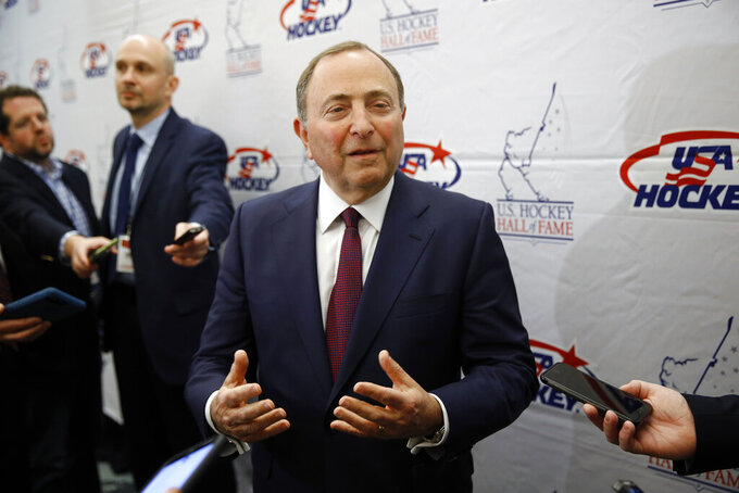 FILE - NHL Commissioner Gary Bettman speaks with members of the media before being inducted into the U.S. Hockey Hall of Fame in Washington, in this Thursday, Dec. 12, 2019, file photo. Like the NBA, the NHL is going forward with a season without a bubble. Commissioner Gary Bettman, Players' Association executive director Don Fehr and other top officials explain how hockey got to this point with a CBA that may have only staved off headaches and playing in mostly empty home arenas to start. (AP Photo/Patrick Semansky, File)