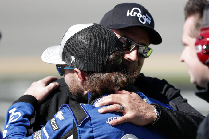 Ricky Stenhouse Jr., left, gets a hug from a crew member after winning the pole position for the Daytona 500 during NASCAR auto race qualifying at Daytona International Speedway, Sunday, Feb. 9, 2020, in Daytona Beach, Fla. (AP Photo/John Raoux)
