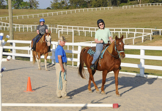 In this Sept. 9, 2019 photo, volunteer Tom Pike coaches Mike Kerns, 13, riding