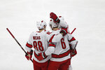 Carolina Hurricanes' Joel Edmunson, center, is congratulated by teammates Martin Necas of the Czech Republic, left, and Nino Niederreiter, right, after Edmunson scored a goal in the first period of an NHL hockey game against the Minnesota Wild, Saturday, Nov. 16, 2019, in St. Paul, Minn. (AP Photo/Stacy Bengs)