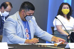 Mississippi Band of Choctaw Indians Chief Cyrus Ben, center, looks at flag design proposals Friday, Aug. 14, 2020, at the Two Mississippi Museums in Jackson, Miss. Ben is part of a nine-member commission that will recommend a new design for a Mississippi state flag, and he says he would like it to include the diamond shape that is important to Choctaw art and culture. Mississippi recently retired the last state flag in the U.S. that included the Confederate battle emblem. (AP Photo/Emily Wagster Pettus)