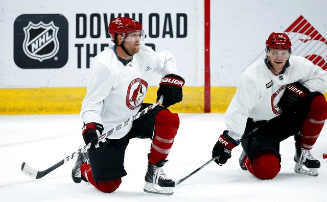 Arizona Coyotes right wing Phil Kessel, left, and Coyotes right wing Christian Fischer (36) take a break during NHL hockey practice at Gila River Arena Monday, July 13, 2020, in Glendale, Ariz. (AP Photo/Ross D. Franklin)