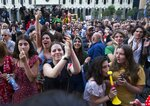 People applaud and listen to a speaker during a protest as opposition demonstrators gather in front of the Georgian Parliament building in Tbilisi, Georgia, Monday, June 24, 2019. Demonstrators have returned to parliament for daily rallies, demanding the release of detained protesters, the ouster of the nation's interior minister and changes in the electoral law to have legislators chosen fully proportionally rather than the current mix of party-list and single-mandate representatives. (AP Photo/Shakh Aivazov)