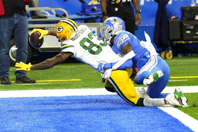 Green Bay Packers wide receiver Marquez Valdes-Scantling (83) defended by Detroit Lions cornerback Amani Oruwariye (24) falls into the end zone for a touchdown during the first half of an NFL football game, Sunday, Dec. 13, 2020, in Detroit. (AP Photo/Paul Sancya)