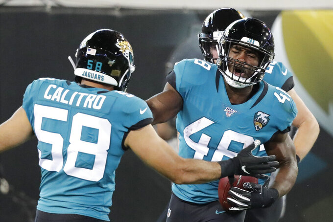 Jacksonville Jaguars outside linebacker Leon Jacobs, center, celebrates with linebacker Austin Calitro (58) after recovering a Tennessee Titans fumble during the first half of an NFL football game, Thursday, Sept. 19, 2019, in Jacksonville, Fla. (AP Photo/John Raoux)