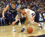 Maine forward Miks Antoms, left, goes after a loose ball with Virginia center Francisco Caffaro during an NCAA college basketball game in Charlottesville, Va., Wednesday, Nov. 27, 2019. (AP Photo/Andrew Shurtleff)
