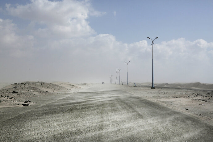 This Feb. 15, 2018, photo shows sand drifting over an empty highway from Abyan to Aden in Yemen. Violence, famine and disease have ravished the country of some 28 million, which was already the Arab world's poorest before the conflict began. The conflict pits a U.S.-backed, Saudi-led coalition supporting the internationally recognized government, which has nominally relocated to Aden but largely lives in exile, against rebels known as Houthis. (AP Photo/Nariman El-Mofty)