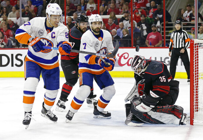 Carolina Hurricanes goalie Curtis McElhinney (35) defends the goal against New York Islanders' Anders Lee (27) and Jordan Eberle (7) while Hurricanes' Justin Faulk watches at rear during the first period of Game 3 of an NHL hockey second-round playoff series in Raleigh, N.C., Wednesday, May 1, 2019. (AP Photo/Gerry Broome)