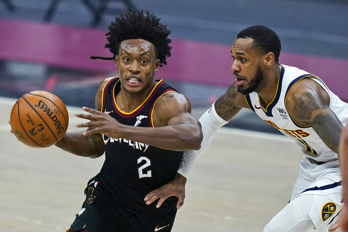 Cleveland Cavaliers' Collin Sexton, left, drives past Denver Nuggets' Monte Morris in the first half of an NBA basketball game, Friday, Feb. 19, 2021, in Cleveland. (AP Photo/Tony Dejak)