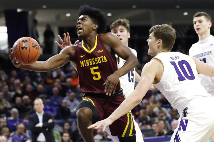Minnesota guard Marcus Carr, left, drives to the basket past Northwestern forward Miller Kopp (10) and center Ryan Young (15) during the first half of an NCAA college basketball game in Evanston, Ill., Sunday, Feb. 23, 2020. (AP Photo/Nam Y. Huh)