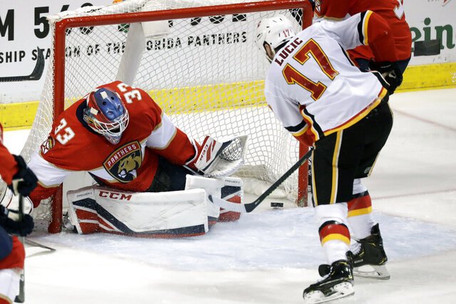 Calgary Flames left wing Milan Lucic (17) scores against Florida Panthers goaltender Sam Montembeault (33) during the second period of an NHL hockey game, Sunday, March 1, 2020, in Sunrise, Fla. (AP Photo/Wilfredo Lee)