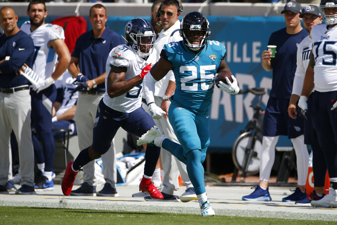 Jacksonville Jaguars running back James Robinson (25) takes off on a long run past Tennessee Titans free safety Kevin Byard, left, during the first half of an NFL football game, Sunday, Oct. 10, 2021, in Jacksonville, Fla. (AP Photo/Stephen B. Morton)
