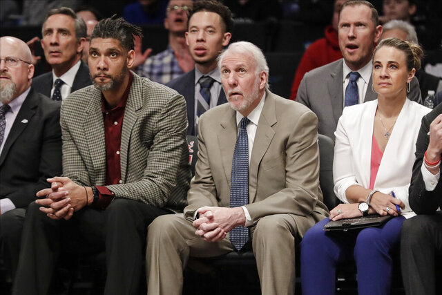 San Antonio Spurs head coach Gregg Popovich, center, watches his players with assistant coaches Becky Hammon, right, and Tim Duncan, left, during the first half of an NBA basketball game against the Brooklyn Nets Friday, March 6, 2020, in New York. (AP Photo/Frank Franklin II)