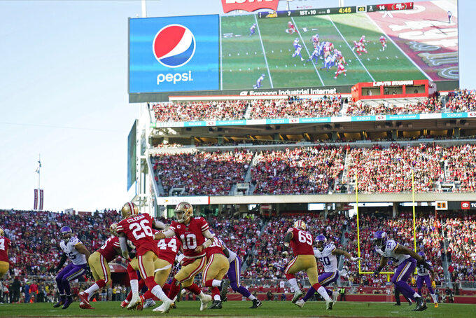 FILE - In this Jan. 11, 2020, file photo, San Francisco 49ers quarterback Jimmy Garoppolo (10) hands off to running back Tevin Coleman (26) during the first half of an NFL divisional playoff football game against the Minnesota Vikings at Levi's Stadium in Santa Clara, Calif. The current collective bargaining agreement expires in March 2021, but NFL owners are eager to get a new contract in place as soon as possible. That would enable them to begin looking toward new, lucrative broadcast deals, with a decade of labor peace assured. But the players don't appear to be in a rush to approve the new agreement that is the result of 10 months of negotiations between the sides. Indeed, several player reps last Friday night were adamant that more negotiating is needed. (AP Photo/Tony Avelar, File)