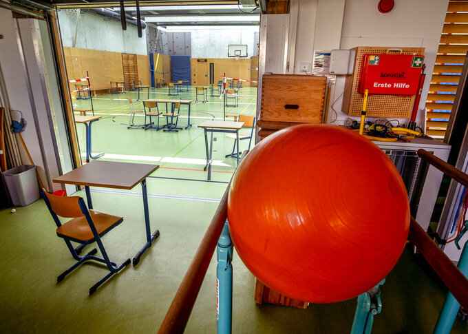 The gym was switched into a class room with more distance in a high school in Frankfurt, Germany, Friday, May 7, 2021. Schools are basically closed to avoid the outspread of the coronavirus, only a few pupils of the graduation classes get face-to-face lessons. (AP Photo/Michael Probst)