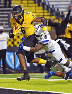 Appalachian State running back Camerun Peoples drags Georgia State safety Chris Moore with him as he scores a touchdown during an NCAA football game, Saturday, Nov. 14, 2020, in Boone, N.C. (Walt Unks/Winston-Salem Journal via AP)