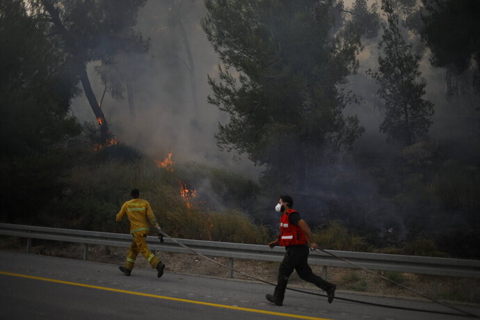 Fire fighters extinguish a forests fire near Kfar Uriya, Thursday, May 23, 2019. Israeli police have ordered the evacuation of several communities in southern and central Israel as wildfires rage amid a major heatwave. (AP Photo/Ariel Schalit)