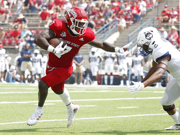 Fresno State running back Jordan Mims, left, stiff-arms a Connecticut defender during the first half of an NCAA college football game in Fresno, Calif., Saturday, Aug. 28, 2021. (AP Photo/Gary Kazanjian)