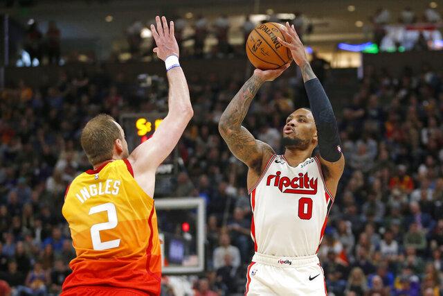 Portland Trail Blazers guard Damian Lillard (0) shoots as Utah Jazz guard Joe Ingles (2) defends during the first half of an NBA basketball game Friday, Feb. 7, 2020, in Salt Lake City. (AP Photo/Rick Bowmer)