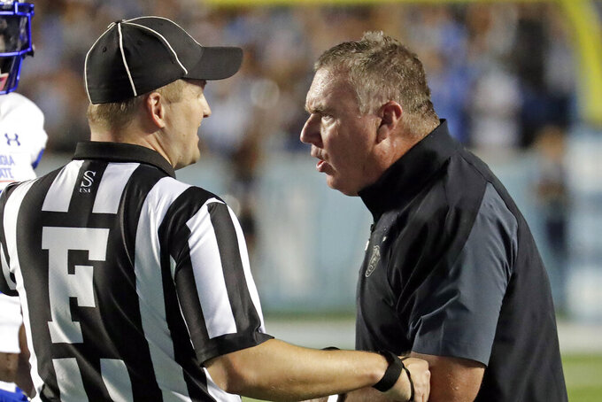 Georgia State head coach Shawn Elliott confers with an official during the first half of an NCAA college football game against North Carolina in Chapel Hill, N.C., Saturday, Sept. 11, 2021. (AP Photo/Chris Seward)