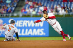 Philadelphia Phillies shortstop Didi Gregorius, right, throws to first base after forcing out Baltimore Orioles' Pat Valaika at second on a fielder's choice hit into by Richie Martin during the sixth inning of an interleague baseball game, Tuesday, Sept. 21, 2021, in Philadelphia. Martin was safe at first on the play. (AP Photo/Matt Slocum)
