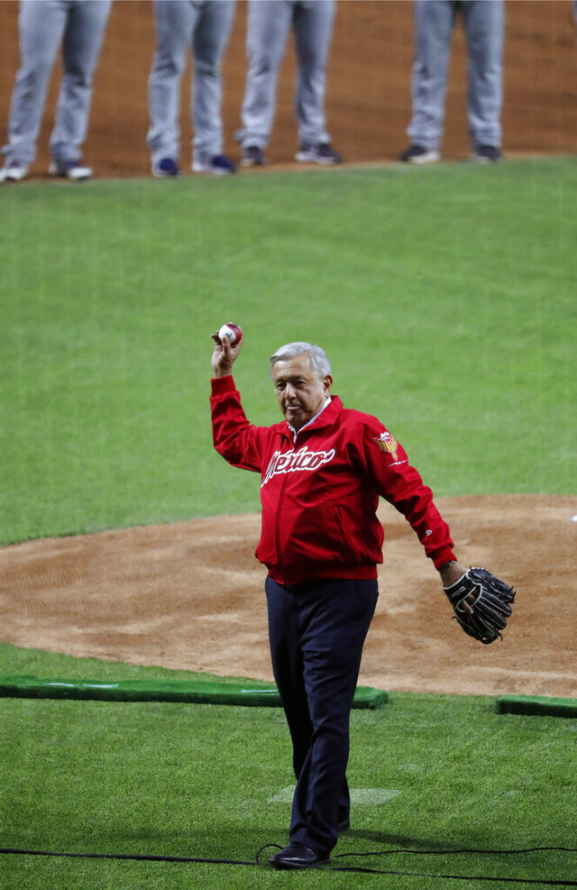 FILE - In this March 23, 2019 file photo, Mexican President Andres Manuel Lopez Obrador throws the first pitch at the inauguration of the Alfredo Harp Helu Stadium, the new home of Los Diablos Rojos baseball team, in Mexico City. Mexican Baseball League announced the cancellation of the 2020 season Wednesday, July 1, the first time in 95 years a whole season had been canceled. (AP Photo/Marco Ugarte, File)