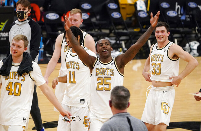Colorado guard McKinley Wright IV, front center, acknowledges the small crowd as he leaves the court with teammates after an NCAA college basketball game against Arizona State, Thursday, March 4, 2021, in Boulder, Colo. (AP Photo/David Zalubowski)