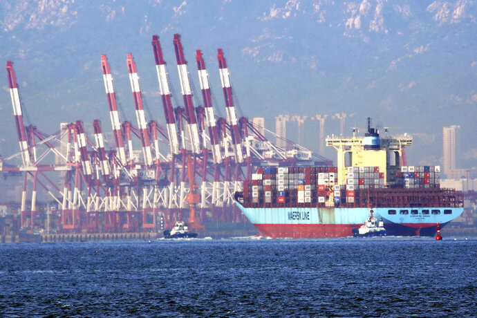In this Oct. 8, 2018, photo, tugboats move a container ship to the dockyard of a seaport in Qingdao in eastern China's Shandong province. Customs data on Friday, Oct. 12, 2018 showed China's trade surplus with the United States widened to a record $34.1 billion September as exports to the U.S. market rose by 13 percent over a year earlier despite a worsening tariff war. (Chinatopix via AP)