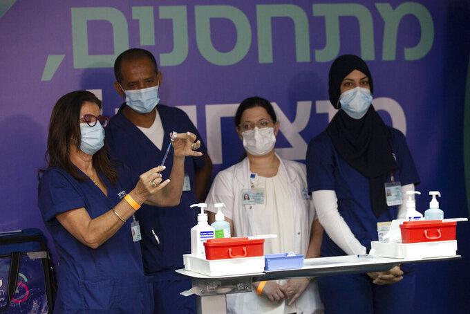 Medical staff prepare COVID-19 vaccines for Israeli President Isaac Herzog and his wife at the Sheba Medical Center in Ramat Gan, Israel, Friday, July 30, 2021. (AP Photo/Maya Alleruzzo, Pool)