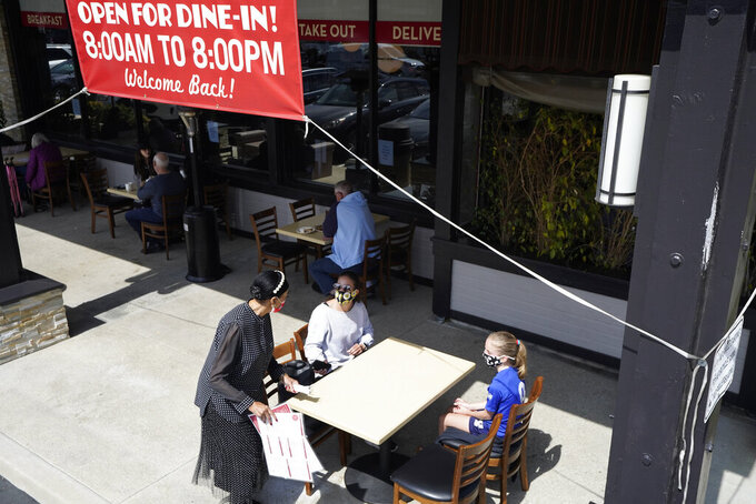 Diners Mandissa Costello, center, and Evie Costello, right, are served by Porsche Milton at Agoura's Famous Deli Sunday, March 14, 2021, in the Agoura Hills section of Los Angeles County. Los Angeles County is reopening businesses to an extent not seen since last spring when a coronavirus surge led to closures of cinemas, gyms, museums and indoor dining. The nation's largest county has been the epicenter of California's deadly winter surge of cases that led to more than 10,500 deaths over two months. A recent plunge in infections, hospitalizations and deaths and a rise in vaccinations has cleared the way for partial reopening that can start as soon as Monday. (AP Photo/Mark J. Terrill)