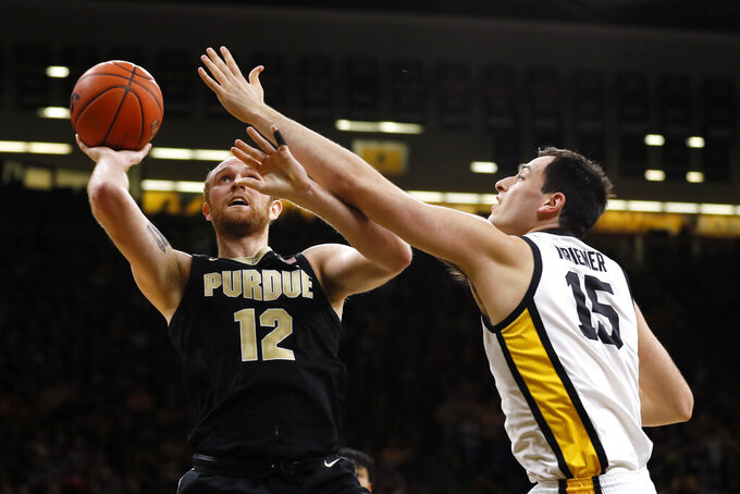 Purdue forward Evan Boudreaux shoots next to Iowa forward Ryan Kriener, right, during the first half of an NCAA college basketball game Tuesday, March 3, 2020, in Iowa City, Iowa. (AP Photo/Charlie Neibergall)