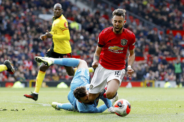 Manchester United's Bruno Fernandes is brought down in the penalty area by Watford goalkeeper Ben Foster, during their English Premier League soccer match at Old Trafford in Manchester, England, Sunday Feb. 23, 2020. Fernandes went on to score from the penalty spot. (Martin Rickett/PA via AP)