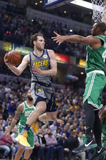Indiana Pacers forward Bojan Bogdanovic, front left, makes a pass around Boston Celtics center Al Horford (42) during the first half of an NBA basketball game in Indianapolis, Friday, April 5, 2019. (AP Photo/Michael Conroy)