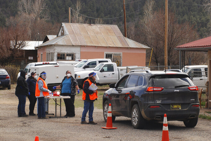 Medical workers and volunteers administer the coronavirus vaccine at a drive-thru immunization clinic at an inn and RV park in Mora, N.M., on Tuesday, April 20, 2021. New Mexico is among the states with the highest rates of vaccination for COVID-19 and efforts are underway to respond to skepticism and misinformation about the effectiveness and risks of immunization. First Lady Jill Biden was kicking off of a visit to the U.S. Southwest with a tour of a vaccination clinic in Albuquerque. (AP Photo/Morgan Lee)