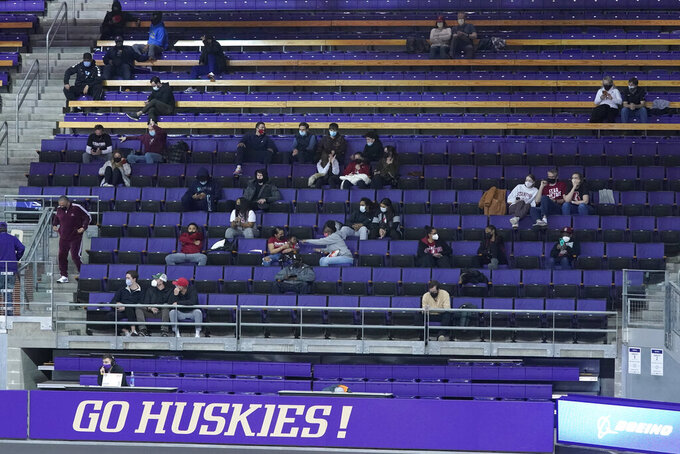 Fans sit in the stands during the first half of an NCAA college basketball game between Washington and Stanford, Thursday, Feb. 18, 2021, in Seattle. For the first time at a Washington home game this season during COVID-19 pandemic, each team was allowed 60 friends or family guests in attendance. (AP Photo/Ted S. Warren)