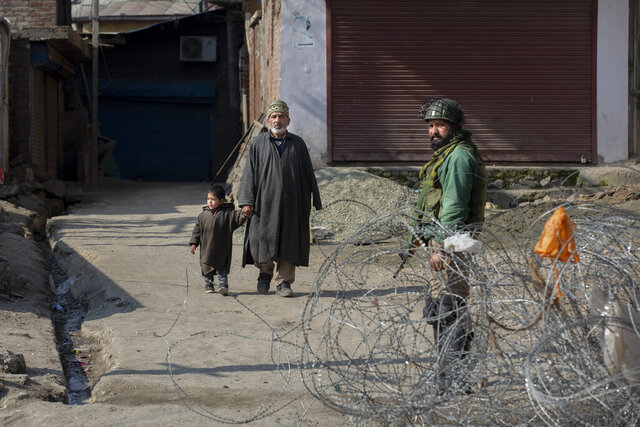 An elderly Kashmiri man along with his grand son walks as Indian paramilitary soldier stands guard near a barbed wire set up as road blockade during a strike in down town Srinagar, Indian controlled Kashmir, Sunday, Feb. 9, 2020. Shops and businesses shut in Indian-controlled Kashmir on Sunday and authorities imposed a lockdown in some parts of the disputed region's main city after separatists called for a strike to mark the execution anniversary of a Kashmiri man who was convicted for an attack on Indian Parliament. (AP Photo/ Dar Yasin)