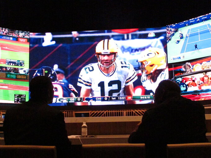 FILE - In this Sept. 5, 2019, file photo, people watching the first NFL game of the season in the sports betting lounge at Bally's casino in Atlantic City N.J. The NFL draft starting on Thursday, April 23, 2020, is expected to be the most heavily wagered-on draft ever, mainly because virtually all major sporting events have been postponed due to the coronavirus outbreak. (AP Photo/Wayne Parry, File)
