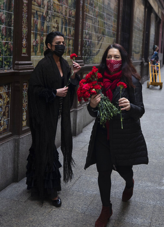 Spanish Flamenco dancer Anabel Moreno, left, is given a rose outside the Villa Rosa Tablao flamenco venue during a protest in Madrid, Spain, Thursday March 4, 2021. The National Association of Tablaos protested outside the mythical Villa Rosa Tablao which has been forced to close permanently due to the covid pandemic. (AP Photo/Paul White)
