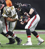 Atlanta Falcons quarterback Matt Ryan struggles to hold on to the ball as New Orleans Saints defensive end Marcus Davenport sacks him during the third quarter of an NFL football game Thursday, Nov. 28, 2019, in Atlanta. (Curtis Compton/Atlanta Journal-Constitution via AP)