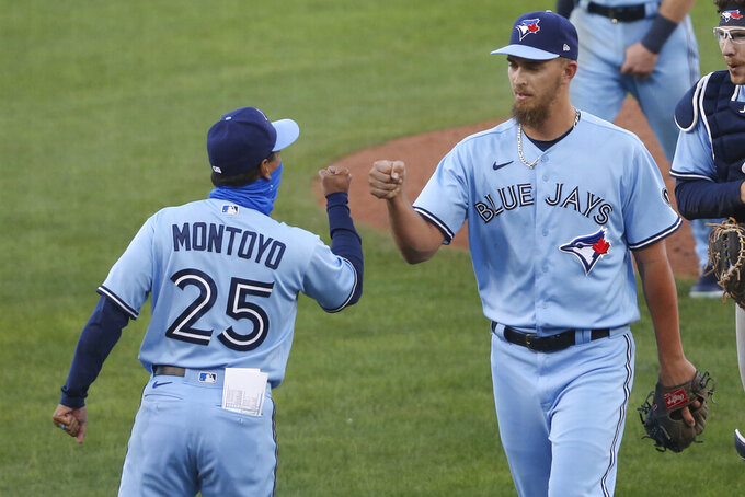 Toronto Blue Jays closing pitcher A.J. Cole and manager Charlie Montoyo celebrate a win over the Philadelphia Phillies following the second game of a baseball doubleheader, Thursday, Aug. 20, 2020, in Buffalo, N.Y. (AP Photo/Jeffrey T. Barnes)
