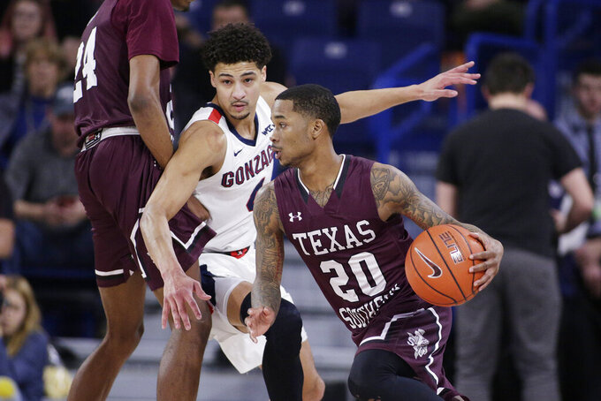 Texas Southern guard Tyrik Armstrong, right, dribbles the ball as forward John Walker III, left, sets a screen on Gonzaga guard Ryan Woolridge during the second half of an NCAA college basketball game in Spokane, Wash., Wednesday, Dec. 4, 2019. Gonzaga won 101-62. (AP Photo/Young Kwak)