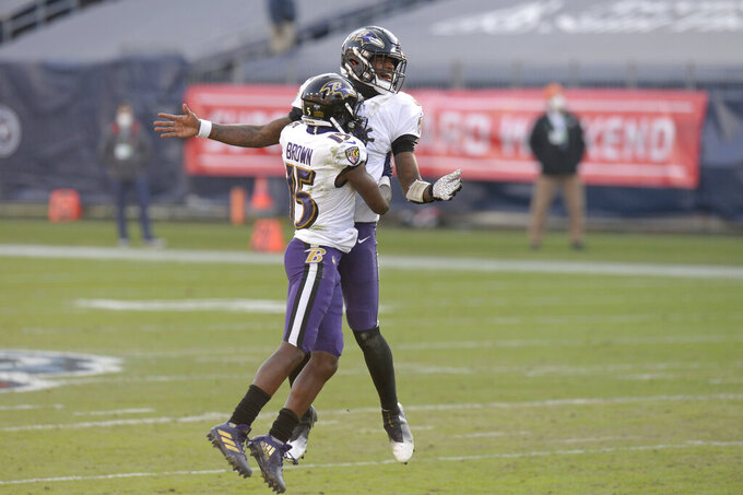 Baltimore Ravens quarterback Lamar Jackson and wide receiver Marquise Brown (15) celebrate after beating the Tennessee Titans in an NFL wild-card playoff football game Sunday, Jan. 10, 2021, in Nashville, Tenn. (AP Photo/Mark Zaleski)