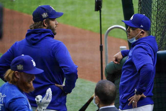Los Angeles Dodgers manager Dave Roberts talks with starting pitcher Clayton Kershaw during batting practice before Game 2 of the baseball World Series against the Tampa Bay Rays Wednesday, Oct. 21, 2020, in Arlington, Texas. (AP Photo/Sue Ogrocki)
