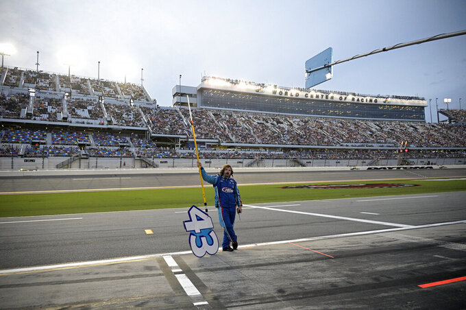 A crew member of driver Erik Jones stands on pit road prior to the start of a NASCAR Cup Series auto race at Daytona International Speedway, Saturday, Aug. 28, 2021, in Daytona Beach, Fla. (AP Photo/Phelan M. Ebenhack)