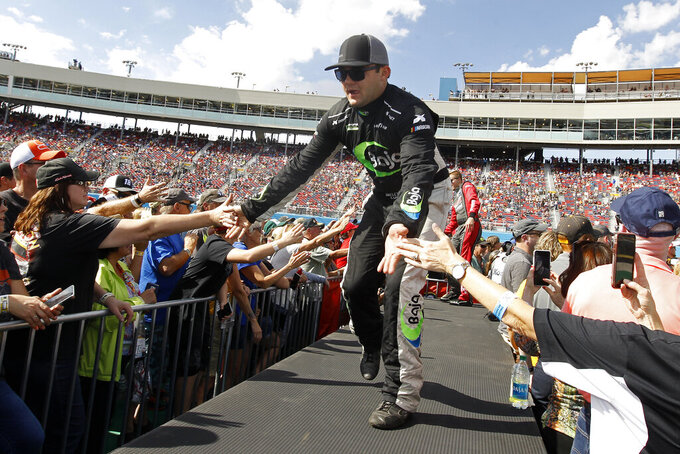 Bayley Currey greets fans during driver introductions prior to the NASCAR Cup Series auto race at ISM Raceway, Sunday, Nov. 10, 2019, in Avondale, Ariz. (AP Photo/Ralph Freso)