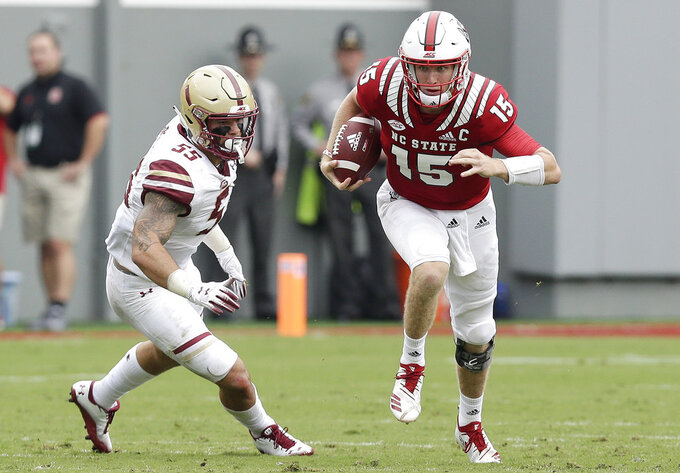 North Carolina State quarterback Ryan Finley (15) runs while Boston College's Isaiah McDuffie (55) misses the tackle during the first half an NCAA college football game in Raleigh, N.C., Saturday, Oct. 6, 2018. (AP Photo/Gerry Broome)