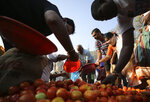 Indians buy vegetables during lockdown in Bangalore, India, Thursday, March 26, 2020. The unprecedented lockdown keeping India's 1.3 billion people at home for all but essential trips to places like supermarkets or pharmacies is meant to keep virus cases from surging above the 553 already recorded and overwhelming an already strained health care system. The new coronavirus causes mild or moderate symptoms for most people, but for some, especially older adults and people with existing health problems, it can cause more severe illness or death. (AP Photo/Aijaz Rahi)