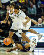 Wake Forest guard Brandon Childress, top, beats Xavier guard Quentin Goodin to a loose ball during the first half of an NCAA college basketball game in Winston-Salem, N.C., Saturday, Dec. 14, 2019. (AP Photo/Nell Redmond)